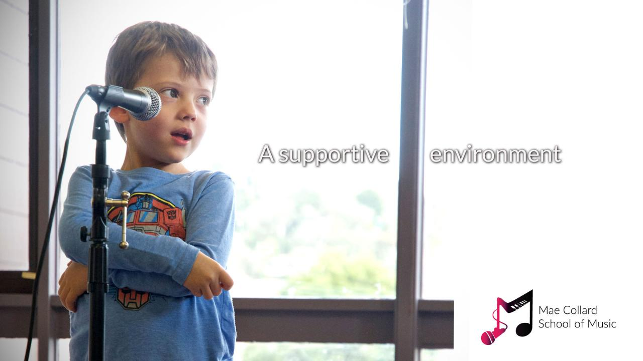 Small boy sings into microphone and looks towards teacher - A supportive environment