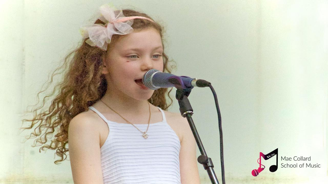 Girl with long curly hair sings confidently into microphone